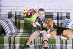 Lustiger Junge mit einem Blumenstrauß von Blumen und von Hundspürhund Stockfotografie