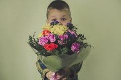 Lustiger Junge mit einem schönen Blumenstrauß von Blumen Lizenzfreie Stockfotos