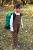 Lustiger Junge steht mit Rucksack Stockfotos