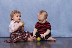 Lustiger Junge und Mädchen mit grünen Früchten Stockfotos