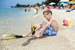 Lustiger Jungentaucher, der auf dem sandigen Strand sich setzt auf Taucherflipper sitzt Stockfotografie
