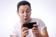 Lustiger junger Asiat Guy Playing Games am Tablet-intelligenten Telefon lizenzfreie stockbilder