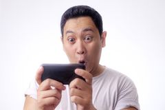 Lustiger junger Asiat Guy Playing Games am Tablet-intelligenten Telefon lizenzfreies stockbild
