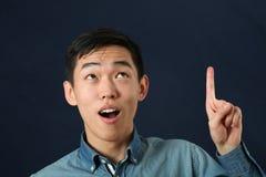 Lustiger junger asiatischer Mann, der aufwärts seinen Zeigefinger zeigt Stockbild