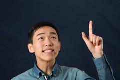Lustiger junger asiatischer Mann, der oben seinen Zeigefinger zeigt Lizenzfreie Stockbilder