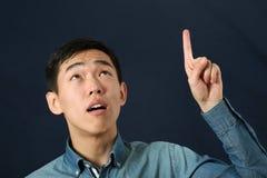 Lustiger junger asiatischer Mann, der sein Zeigefinger upwa zeigt Lizenzfreie Stockfotografie