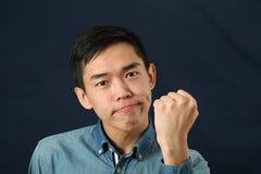 Lustiger junger asiatischer Mann, der seine Faust rüttelt Stockfotos