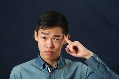 Lustiger junger asiatischer Mann, der seinen Zeigefinger zeigt Stockfoto