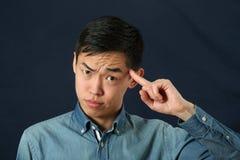 Lustiger junger asiatischer Mann, der seinen Zeigefinger zeigt Stockbilder