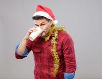 Lustiger junger getrunkener Mann, der Sankt-Hut hält eine Papierschale trägt Stockfoto