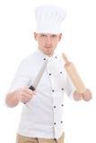 Lustiger junger Mann in der Chefuniform mit hölzernem Backennudelholz a Stockbild