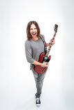 Lustiger junger Mann, der E-Gitarre singt und spielt Stockfoto