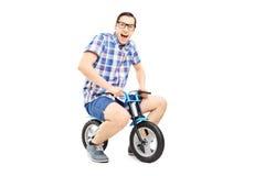 Lustiger junger Mann, der ein kleines Fahrrad reitet Lizenzfreies Stockfoto