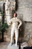 Lustiger Kerl, der mit einer Statue ohne einen Kopf aufwirft Lizenzfreie Stockfotografie