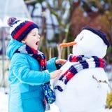 Lustiger Kinderjunge in der bunten Kleidung, die einen Schneemann, draußen macht lizenzfreies stockfoto