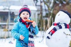 Lustiger Kinderjunge in der bunten Kleidung, die einen Schneemann, draußen macht Stockfotografie