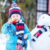 Lustiger Kinderjunge in der bunten Kleidung, die einen Schneemann, draußen macht Lizenzfreie Stockfotografie