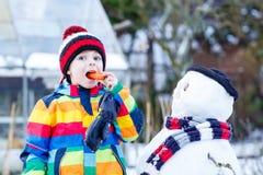 Lustiger Kinderjunge in der bunten Kleidung, die einen Schneemann, draußen macht Stockfotos