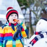 Lustiger Kinderjunge in der bunten Kleidung, die einen Schneemann, draußen macht Stockbilder