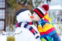 Lustiger Kinderjunge in der bunten Kleidung, die einen Schneemann, draußen macht Stockbild
