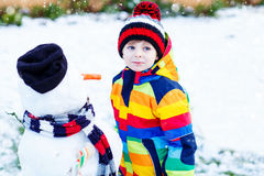 Lustiger Kinderjunge in der bunten Kleidung, die einen Schneemann macht Stockbilder