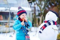 Lustiger Kinderjunge, der draußen einen Schneemann im Winter macht Stockbild