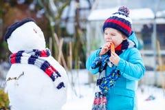 Lustiger Kinderjunge, der draußen einen Schneemann im Winter macht Stockbilder