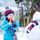 Lustiger Kinderjunge, der draußen einen Schneemann im Winter macht Stockfotos