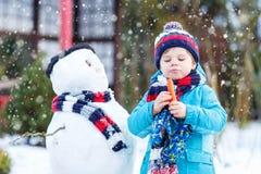 Lustiger Kinderjunge, der draußen einen Schneemann im Winter macht Stockfoto