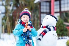 Lustiger Kinderjunge, der draußen einen Schneemann im Winter macht Lizenzfreies Stockbild