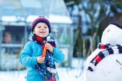 Lustiger Kinderjunge, der draußen einen Schneemann im Winter macht Lizenzfreie Stockfotografie