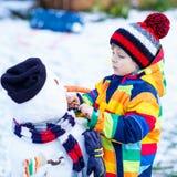 Lustiger Kinderjunge, der einen Schneemann im Winter macht Lizenzfreies Stockfoto
