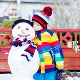 Lustiger Kinderjunge, der einen Schneemann im Winter macht Lizenzfreies Stockbild
