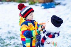 Lustiger Kinderjunge, der einen Schneemann im Winter macht Stockbild