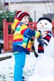 Lustiger Kinderjunge, der einen Schneemann im Winter macht Lizenzfreie Stockfotos