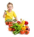 Lustiger Kinderjunge, der Gemüse isst. Gesundes Lebensmittel. Stockbild