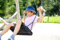 Lustiger Kinderjunge, der Spaß mit dem Kettenschwingen auf Spielplatz im Freien beim Sein nasses gespritzt mit Wasser hat Stockfotos