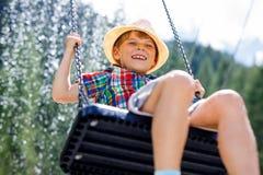 Lustiger Kinderjunge, der Spaß mit dem Kettenschwingen auf Spielplatz im Freien beim Sein nasses gespritzt mit Wasser hat Lizenzfreie Stockbilder