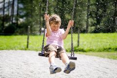 Lustiger Kinderjunge, der Spaß mit dem Kettenschwingen auf Spielplatz im Freien beim Sein nasses gespritzt mit Wasser hat Lizenzfreie Stockfotografie