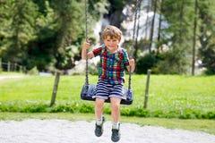 Lustiger Kinderjunge, der Spaß mit dem Kettenschwingen auf Spielplatz im Freien beim Sein nasses gespritzt mit Wasser hat Lizenzfreies Stockbild
