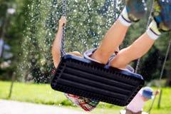 Lustiger Kinderjunge, der Spaß mit dem Kettenschwingen auf Spielplatz im Freien beim Sein nasses gespritzt mit Wasser hat Stockfoto
