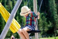 Lustiger Kinderjunge, der Spaß mit dem Kettenschwingen auf Spielplatz im Freien beim Sein nasses gespritzt mit Wasser hat Stockbild
