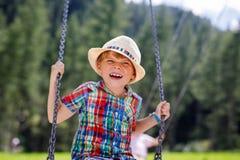 Lustiger Kinderjunge, der Spaß mit dem Kettenschwingen auf Spielplatz im Freien beim Sein nasses gespritzt mit Wasser hat Stockbilder