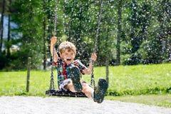 Lustiger Kinderjunge, der Spaß mit dem Kettenschwingen auf Spielplatz im Freien beim Sein nasses gespritzt mit Wasser hat Stockfotografie