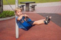 Lustiger Kinderjunge, der Spaß mit Kettenschwingen auf Spielplatz im Freien hat Stockfoto