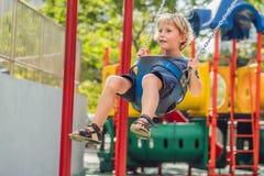 Lustiger Kinderjunge, der Spaß mit Kettenschwingen auf Spielplatz im Freien hat Lizenzfreie Stockfotos