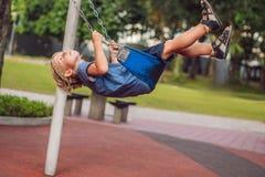 Lustiger Kinderjunge, der Spaß mit Kettenschwingen auf Spielplatz im Freien hat Stockfotos