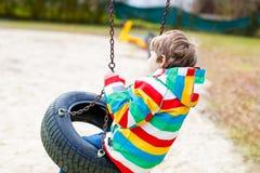 Lustiger Kinderjunge, der Spaß mit Kettenschwingen auf Spielplatz im Freien hat Lizenzfreie Stockbilder