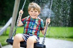 Lustiger Kinderjunge, der Spaß mit Kettenschwingen auf Spielplatz im Freien während des Regens hat Stockfotografie