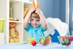 Lustiger Kinderjunge, der zu Hause Gemüse isst Lizenzfreie Stockfotografie